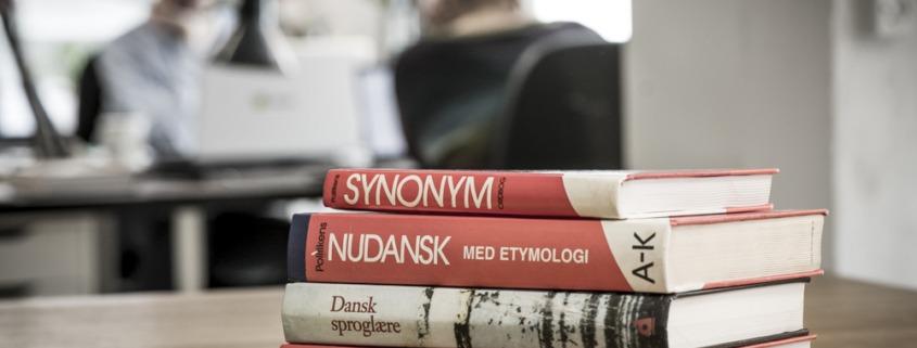 Foto af en bogstak med bl.a. Nudansk Ordbog