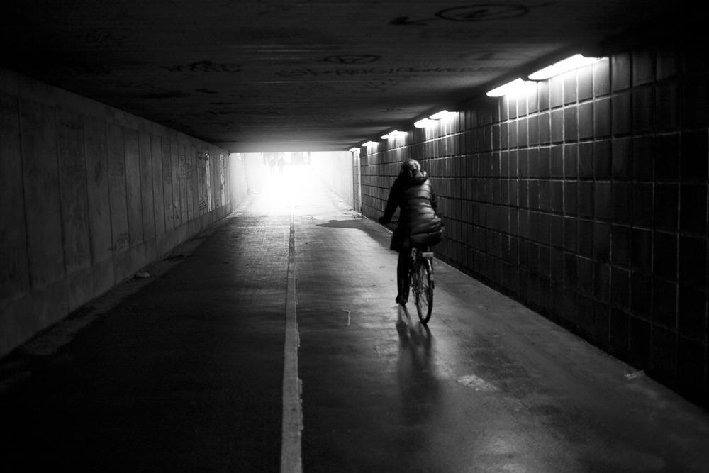 Fotografi af en kvinde, der cykler under en bro