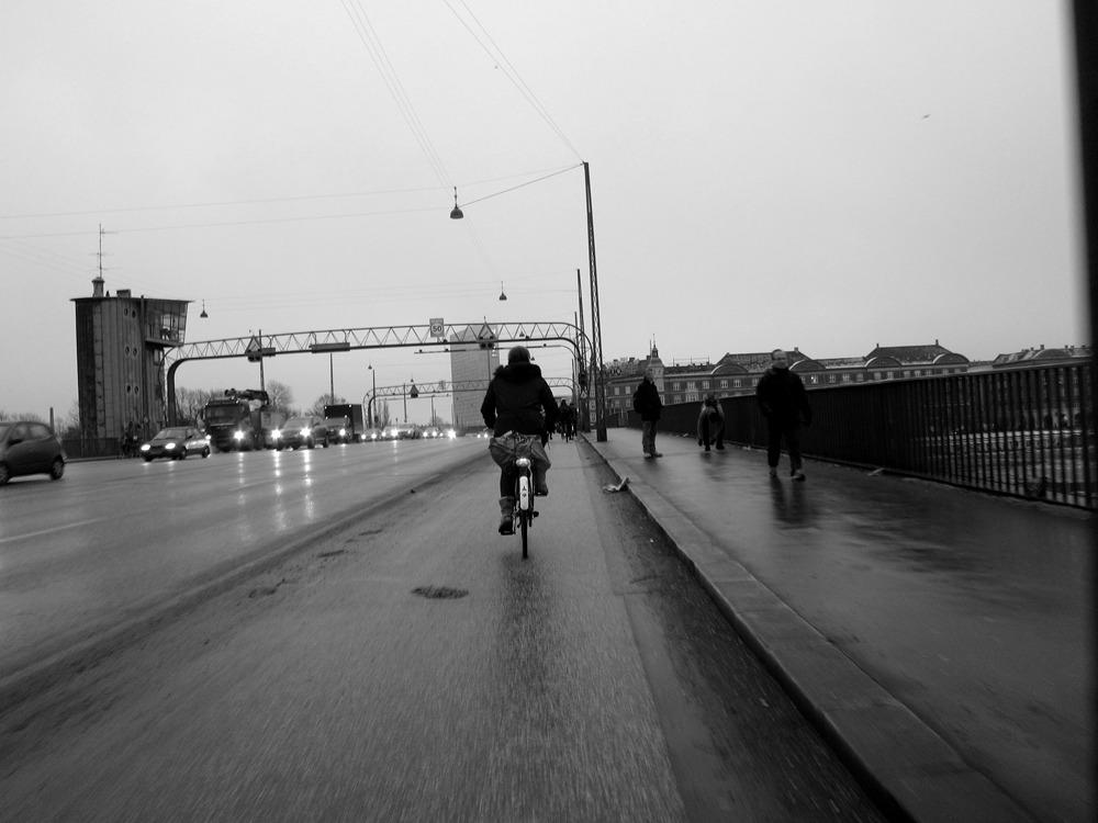 Fotografi af en mand, der cykler over en bro