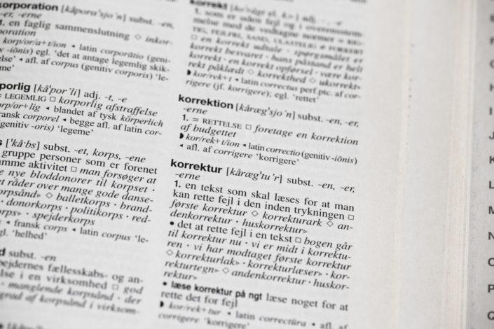 Et close-up af ordet korrektur fra Nudansk Ordbog