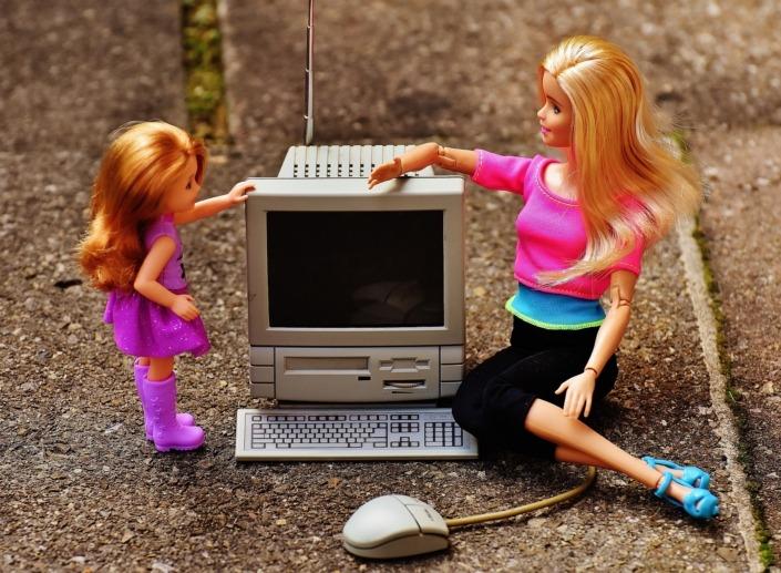 To barbie-dukker sidder foran en computer